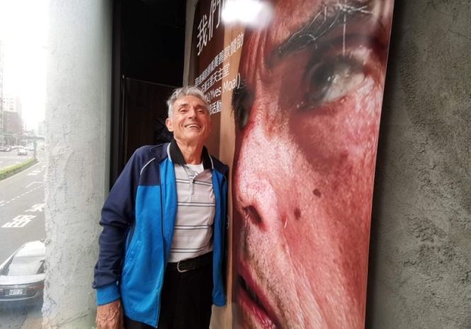 Fr. Yves Moal stands next to his huge photo!
